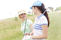 Popular : Happy female golfers talking at golf course