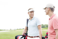 Popular : Happy golfer communicating with male friend against clear sky
