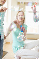 Happy mother and children playing with bubble wands at home