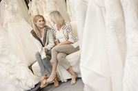 Happy mother and daughter sitting with footwear on sofa in bridal store