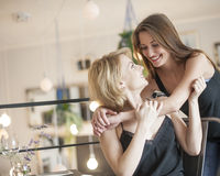 Happy woman embracing female friend in cafe