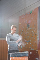 Popular : Low angle view of confident man dusting powder by climbing wall in crossfit gym