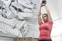 Low angle view of dedicated woman lifting kettlebell in crossfit gym