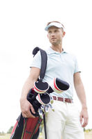 Popular : Low angle view of thoughtful mid-adult man carrying golf club bag against clear sky