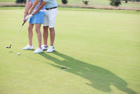 Popular : Low section of couple playing golf