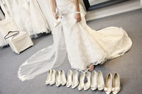 Low section of young woman standing with variety of footwear in bridal boutique