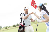 Popular : Male and female friends giving high-five at golf course
