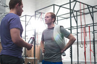 Popular : Male friends talking in crossfit gym