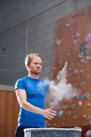 Popular : Man dusting powder by climbing wall in crossfit gym