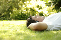 Man listening to music on the headphones while lying on the field