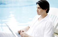 Man sitting by the pool side using laptop
