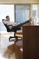 Man sitting in office with feet up on desk using mobile phone
