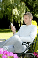 Man sitting on the bench listening to music on the mp3