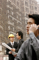 Man talking on the hand phone while his colleague talking to the architect