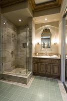 Marble shower cubicle with tiled green floor