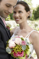 Mid adult bride and groom holding bouquet smiling