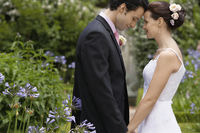 Mid adult bride and groom in garden face to face side view