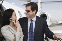 Mid-adult businesswoman and businessman flirting in front of airplane