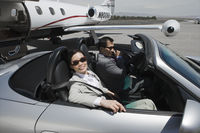 Mid-adult businesswoman and mid-adult businessman sitting in convertible on landing strip