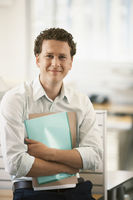 Mid-adult male office worker sitting by cubicle holding files portrait