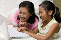Mother and daughter in living room using laptop together