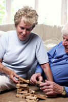 Old couple playing with building blocks
