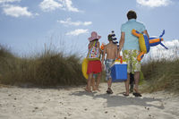 Parents and three children  6-11  carrying beach accessories back view