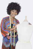 Portrait of african american female fashion designer with tailor s dummy over gray background