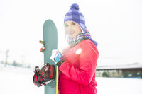 Portrait of beautiful young woman holding snowboard in snow