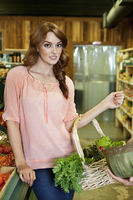 Portrait of beautiful young woman with basket in supermarket