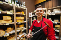 Portrait of confident male salesperson holding knife in cheese store