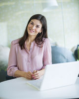 Portrait of confident young businesswoman with laptop at office table