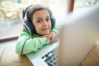 Portrait of cute girl listening to music on headphones with laptop at table