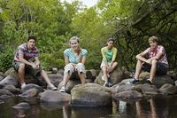Popular : Portrait of four teenagers  16-17 years  sitting on stones by river