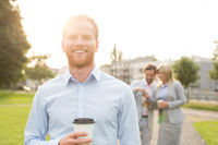 Popular : Portrait of happy businessman holding disposable cup with colleagues standing in background