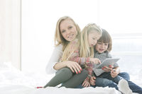 Portrait of happy mother with children using digital tablet in bedroom