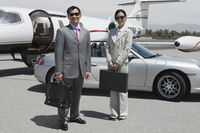 Portrait of mid-adult businesswoman and mid-adult businessman standing in front of private plane on landing strip