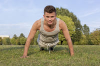 Popular : Portrait of young man doing pushups in park