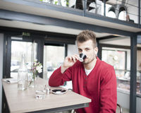 Portrait of young man drinking espresso in cafe