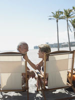 Senior couple on sunloungers on tropical beach back view