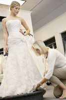 Senior employee adjusting wedding dress of beautiful young bride in bridal store