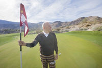 Popular : Senior male golfer looking away while holding flag and putter at golf course
