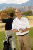 Popular : Senior man holding golf club standing on golf course