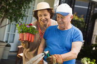 Senior woman assisting husband watering plants in garden
