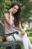 Serious young woman using cell phone on park bench