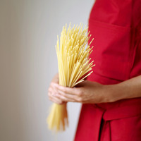Popular : Side view of a lady in red apron holding some spaghetti