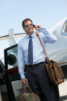 Smiling businessman standing beside car near private jet talking on mobile before leaving on business trip