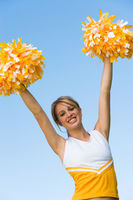 Smiling cheerleader rising pom-poms  portrait   low angle view