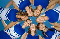 Popular : Smiling cheerleaders standing in circle  portrait   view from below