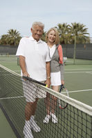 Smiling couple standing on tennis court near net holding rackets